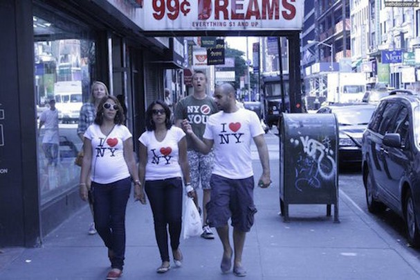 Three tourists in 'I love New York' t-shirts right in front of the guy with the slogan 'New York doesn't need you'